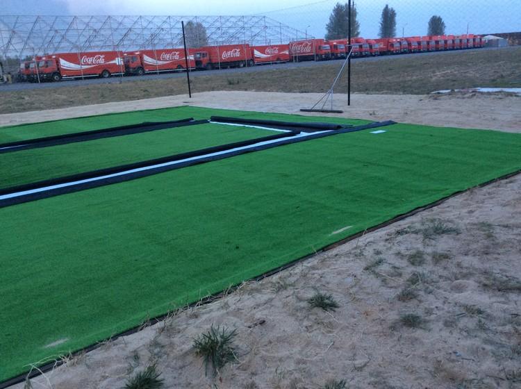 Укладка искусственной травы на волейбольной площадке завода Кока-Кола